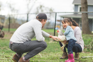 Happy Family Playing with a Chicken in the Yard of their Naples Rental Home