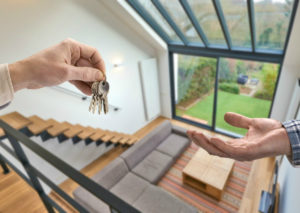 Resident Handing Keys to a Guest After Subletting Your Wixom Rental Property as an Airbnb