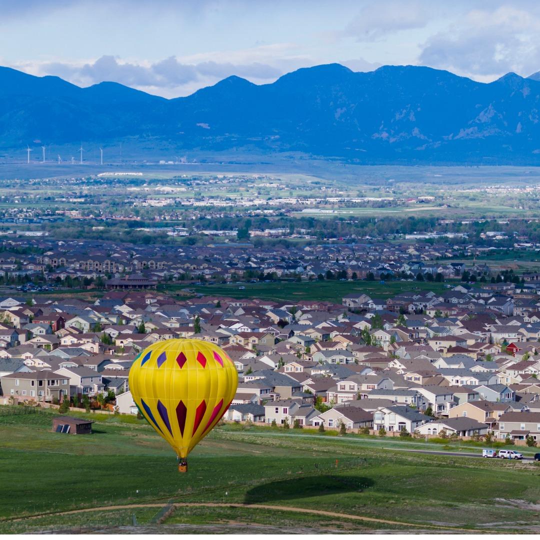 Hot air balloon floating over neighborhood in Erie, Colorado