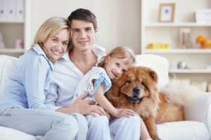 Happy Family Posing on a White Couch with their Dog