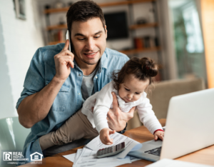 Remote Worker Holding His Baby While Working from Home