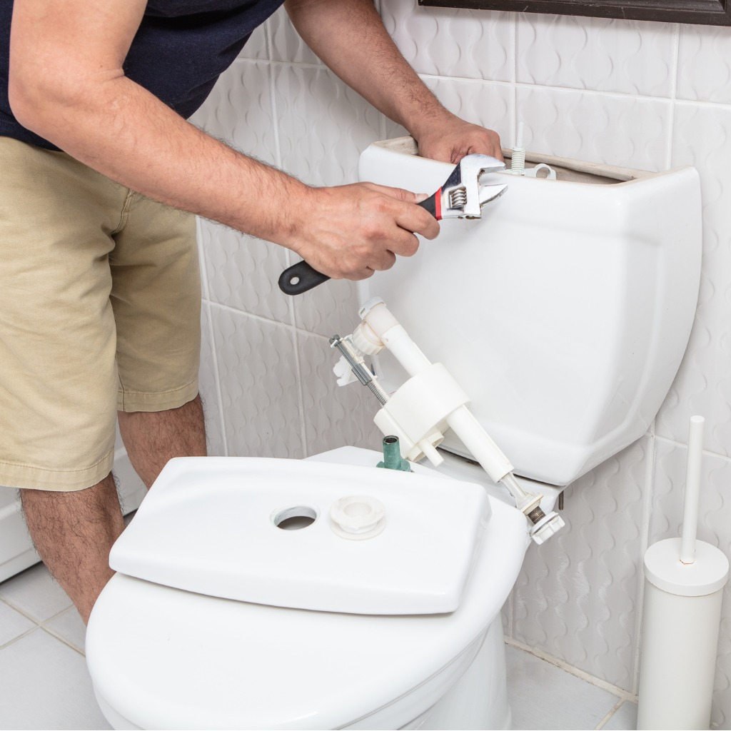 man using wrench repairing toilet cistern