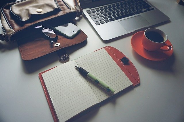 Laptop next to a cup of coffee and a blank notepad