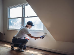 man painting apartment interior