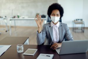 Real Estate Agent Sitting At Desk With Face Mask