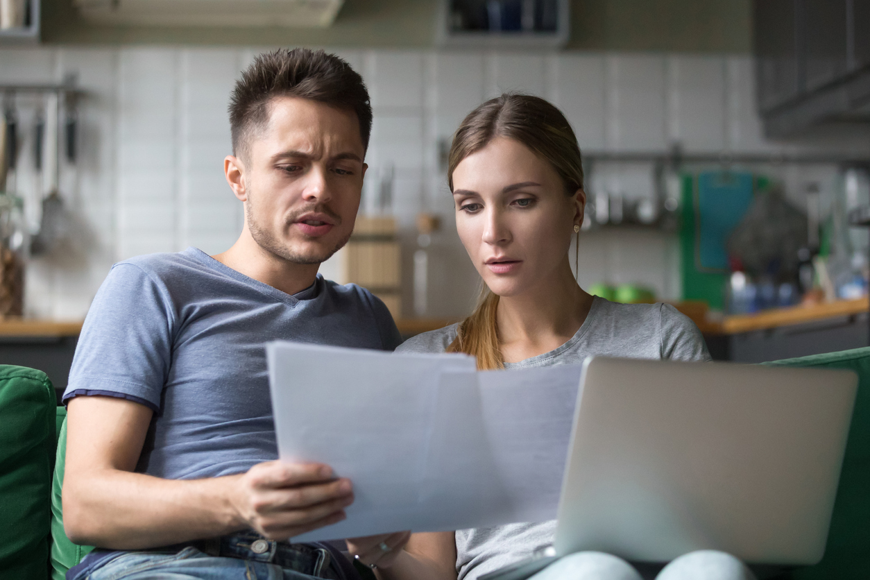 Serious confused couple checking domestic bills with papers and laptop