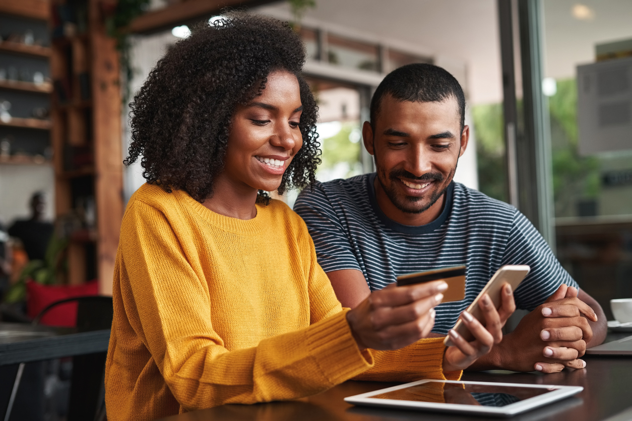Man looking at his girlfriend shopping online in cafe