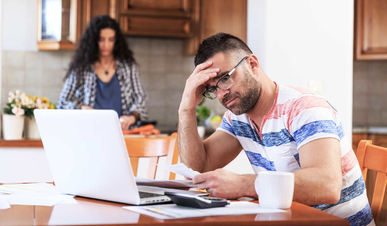 Couple doing home budgeting, using laptop, having problems.