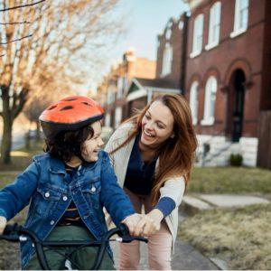 mother teaching son to ride his bike in Fallon, MO.