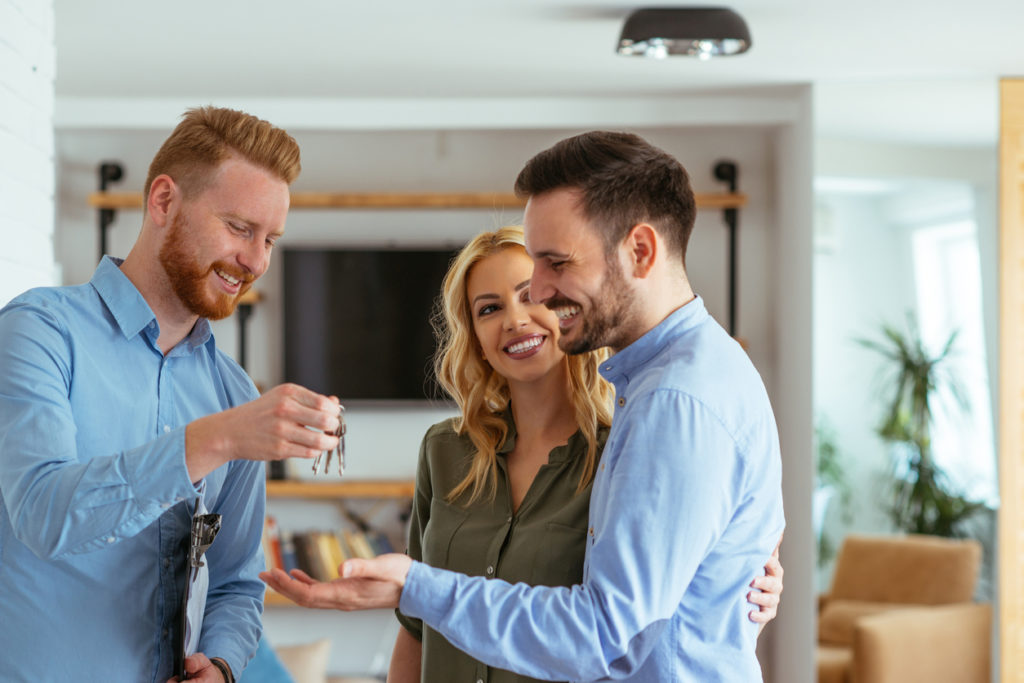 Property manager handing residence keys to young couple