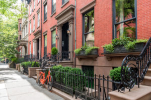 Two bicycles in front of a brownstone building