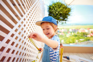 Young Milwaukee Resident Measuring the Trellis on an Outdoor Patio