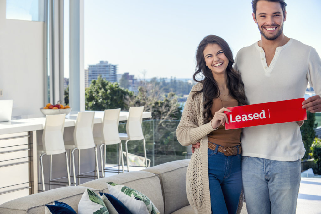 Young couple holding a leased rental sign in a luxury home.