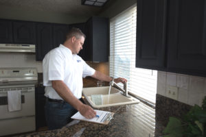 Real Property Management Gold staff inspecting the sink