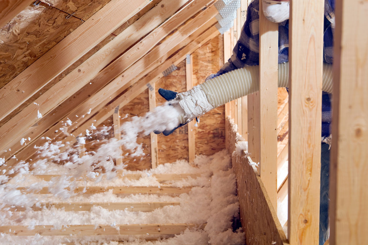 Spraying Blow-In Fiberglass Insulation Between the Attic Trusses of Your Warren Rental Home
