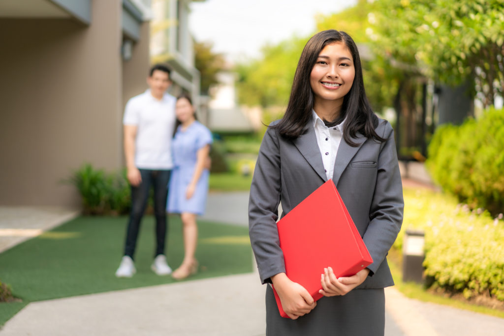 confident real estate agent holding a red file