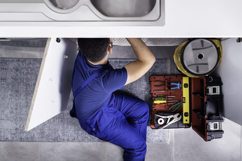 Plumber Fixing an Emergency Leak Under the Sink
