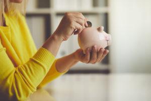 Plano Woman Saving Change in a Piggy Bank