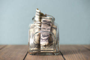 Mason Jar with Several Dollar Bills Stuffed Inside as an Emergency Fund