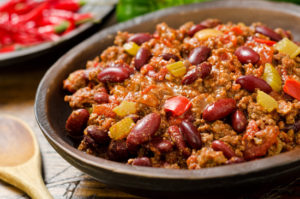 A hearty bowl of chili con carne with hot peppers.