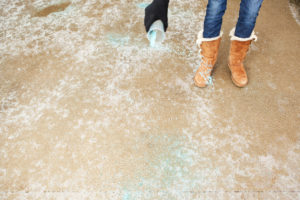 Chesterfield County Resident Spreading Salt on an Icy Winter Driveway
