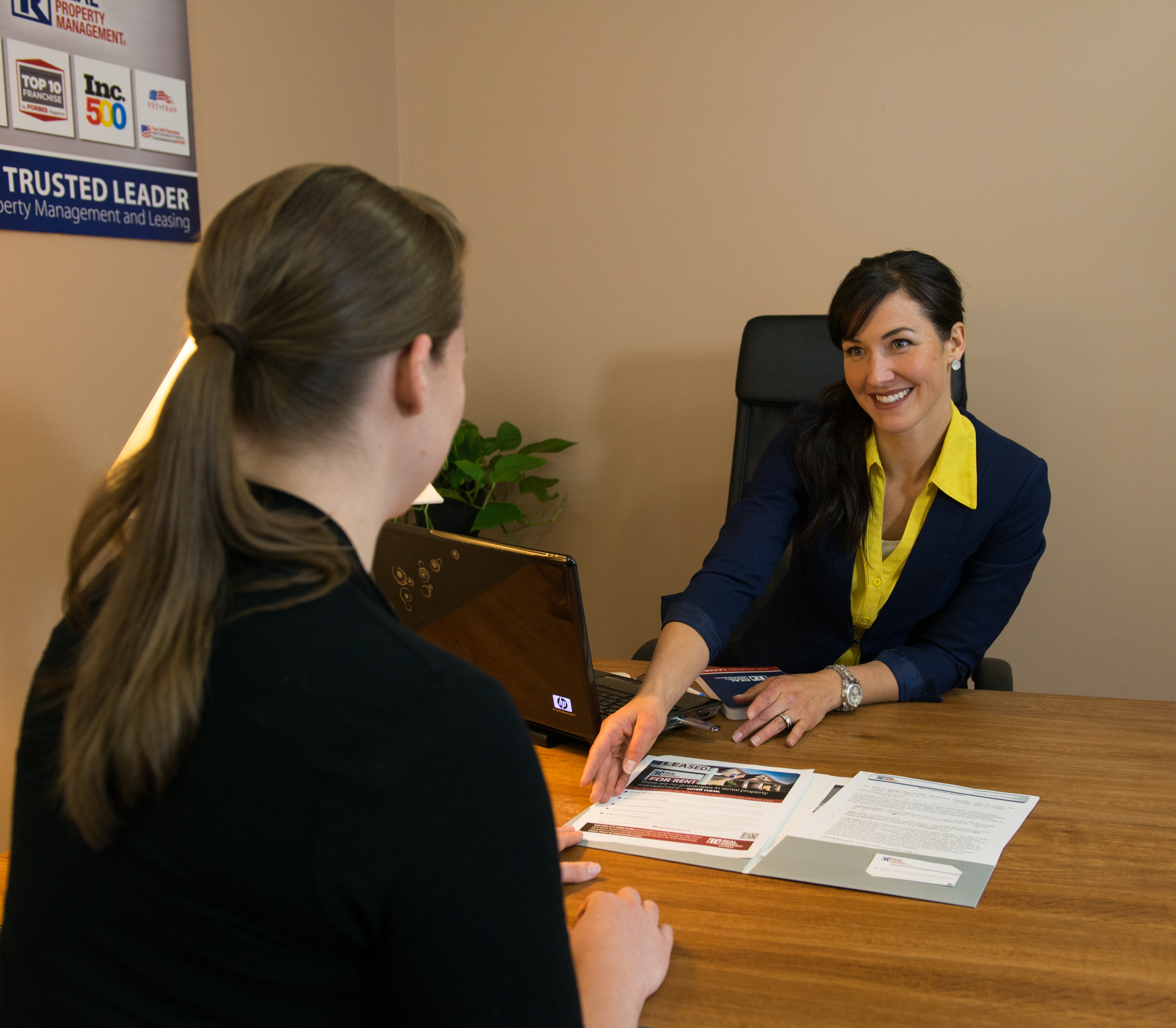 A Potential Resident Sitting at a Desk with a Real Property Management Raleigh Manager