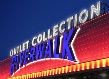 RSM Design Environmental Experiential Architectural Graphic Design Project Portfolio The Outlet Collection At RIverwalk New Orleans LA Retail And Entertainment Exterior Building Identity Wall Mounted Facsia Sign Neon View Night Signage