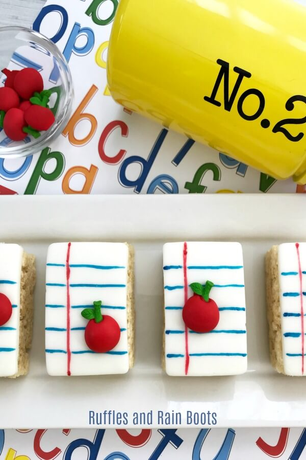 These fun notebook paper Rice Krispies Treats are a great way to ring in the new school year or show a teacher appreciation. #teachers #backtoschool #treatideas #ricekrispies #ricekrispiestreats #rufflesandrainboots