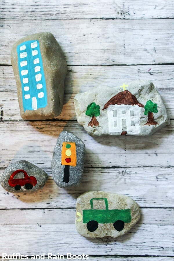 Make these rock village story stones with the kids. It's a fun rock painting idea for kindness rocks when placed all together! #rockpainting #rockpainting101 #rockpaintingideas #storystones #rufflesandrainboots