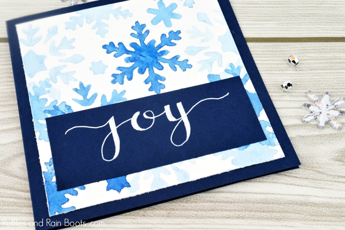 handmade watercolor painted snowflake stencil card with joy in hand written text
