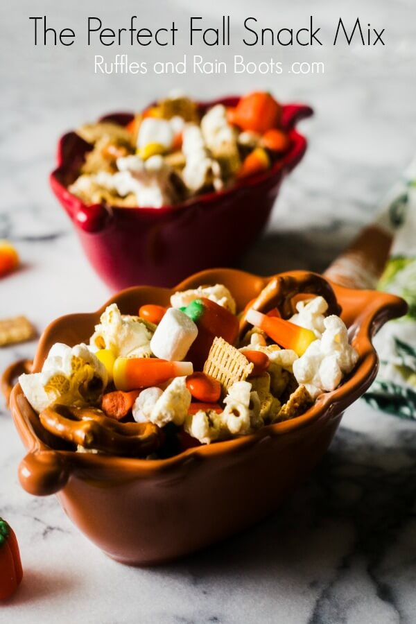 fall snack mix with popcorn pretzels marshmallows and candy in a leaf bowl on a marble table top