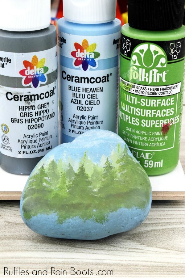 picture of 3 tubes of paint and a semi painted forest rock