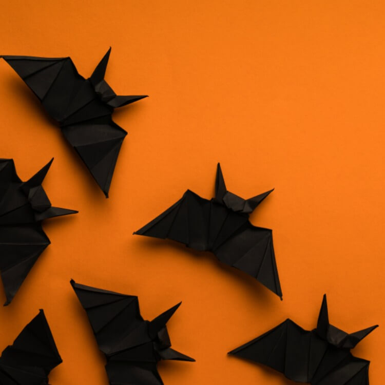 black origami bats on orange background