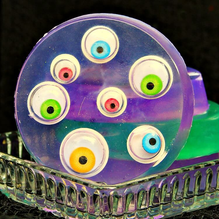 close up of purple melt and pour monster soap with googly eyes in a clear soap dish