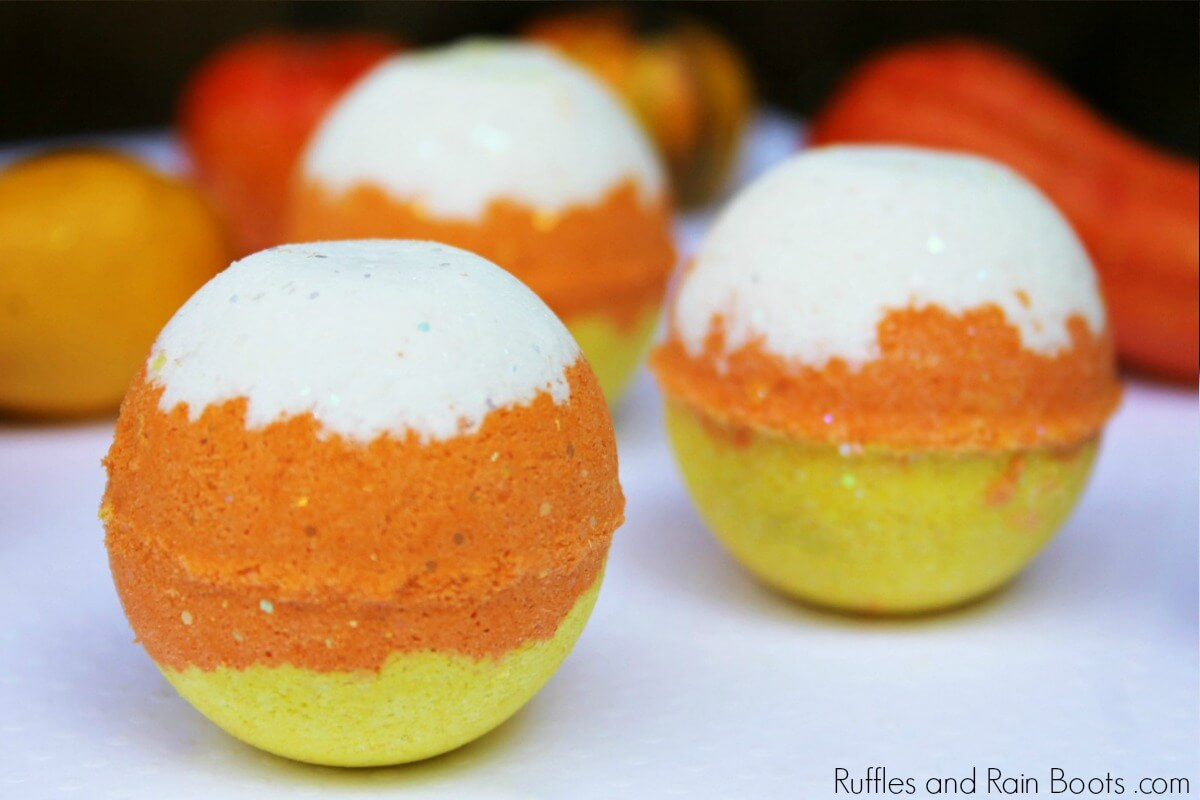 three candy corn colored bath bombs on a white table