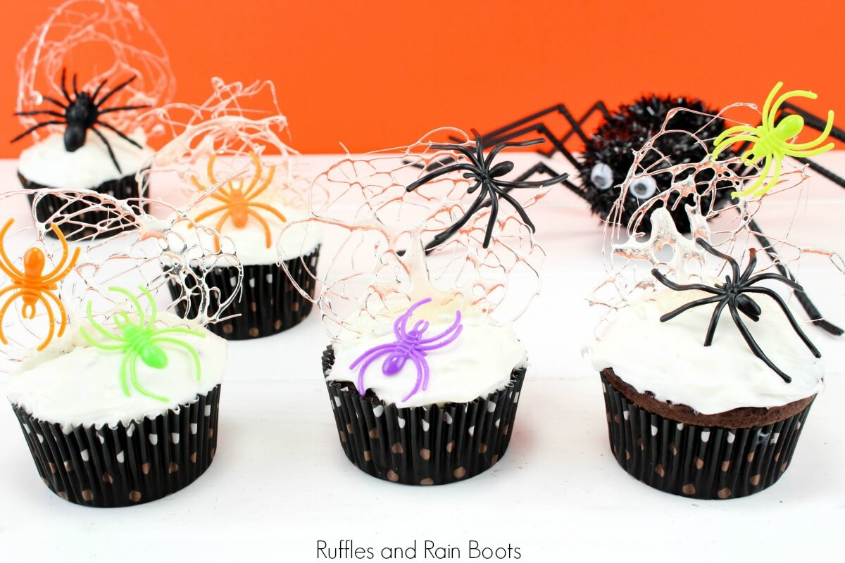 adorable Halloween spun sugar cupcakes with spiders on white background with text which reads Ruffles and Rain Boots