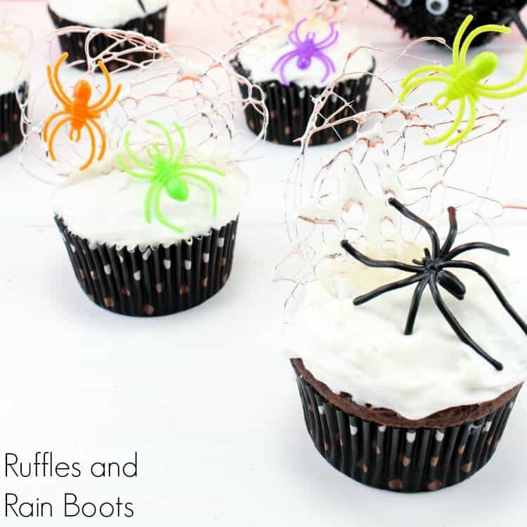 sugar spun spider web cupcakes with marshmallow frosting and plastic spiders with text which reads Ruffles and Rain Boots