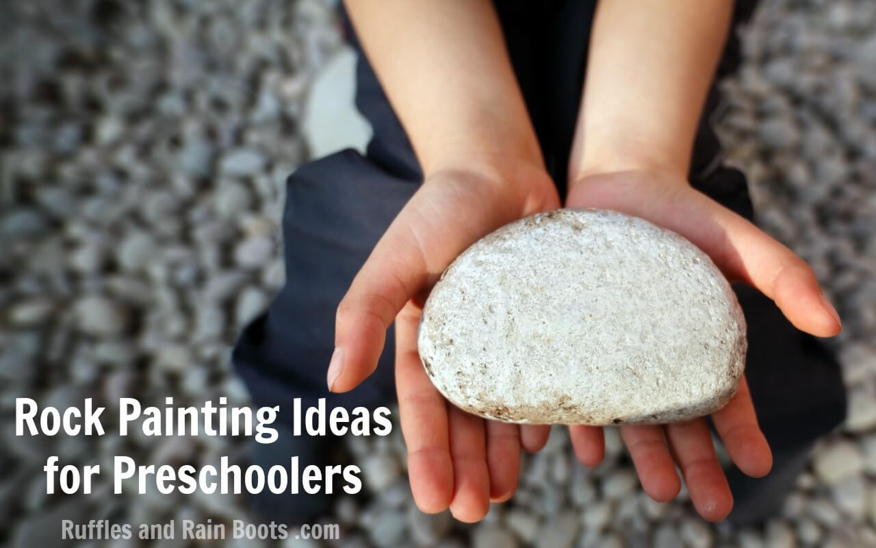 child on beach holding large rock with text which reads Rock Painting Ideas for Preschoolers