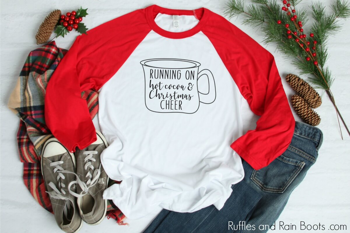 red raglan t shirt on Christmas background with mug drawing and text which reads Running on Hot Cocoa and Christmas cheer