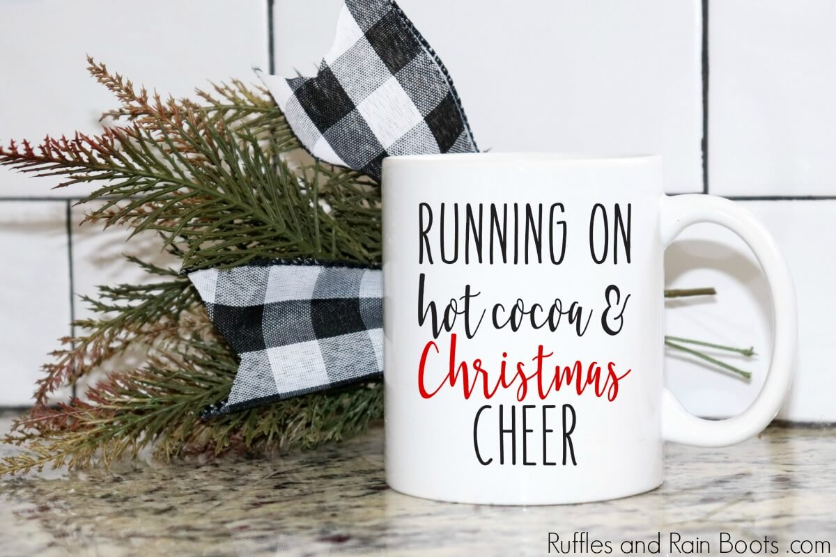 coffee mug on counter with Buffalo check bow and mug which reads Running on Hot Cocoa and Christmas Cheer free SVG