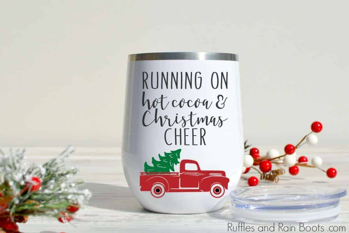 close up of Christmas gift tumbler with berries on marble background with text which reads Running on hot cocoa and Christmas cheer