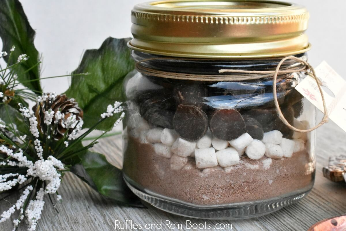close up photo of mason jar hot cocoa gift with greenery on wooden table