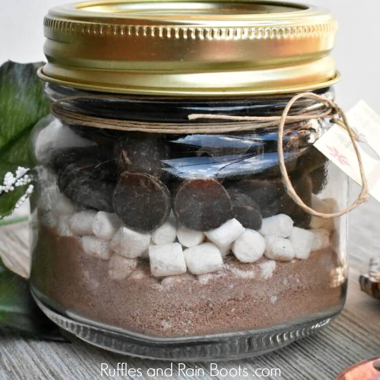 close up of layered hot cocoa gift in mason jar with text which reads Ruffles and Rain Boots .com