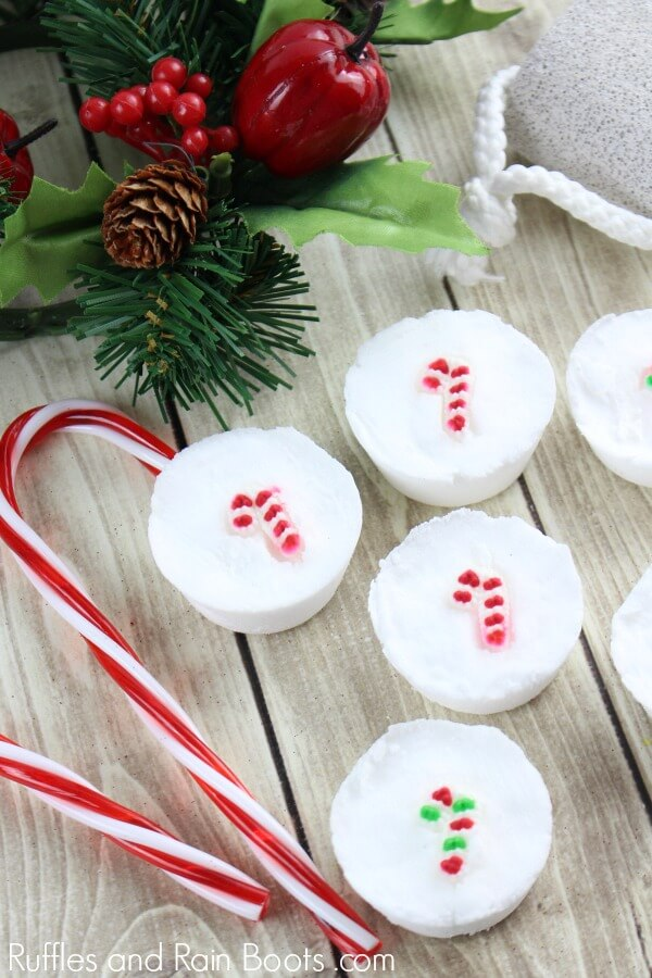 Christmas shower fizzies on wood background with holiday garland and candy canes