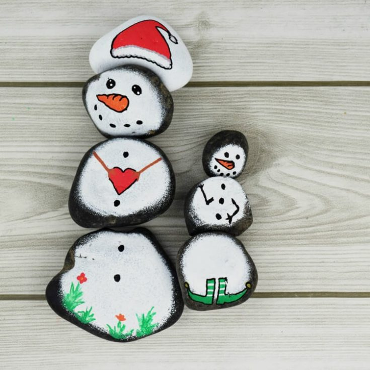 Snowman Story Stones Rock Painting on wood background