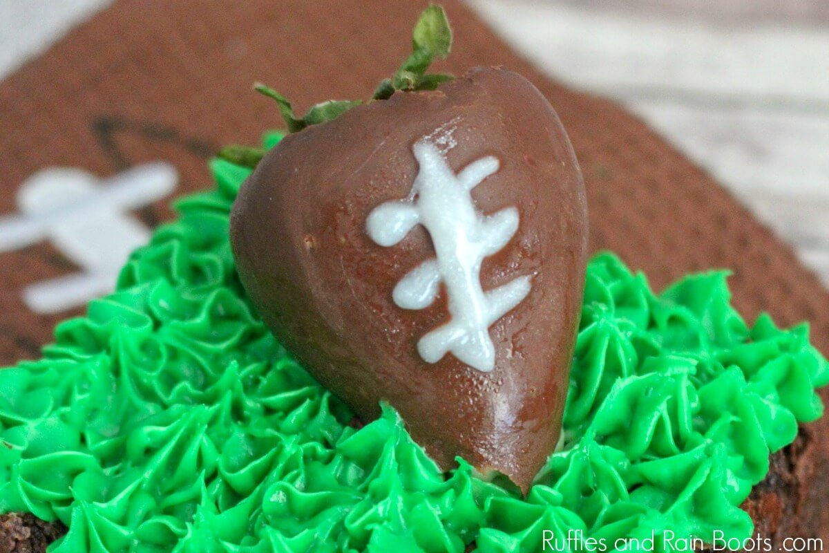 close up of chocolate covered strawberry on football brownie