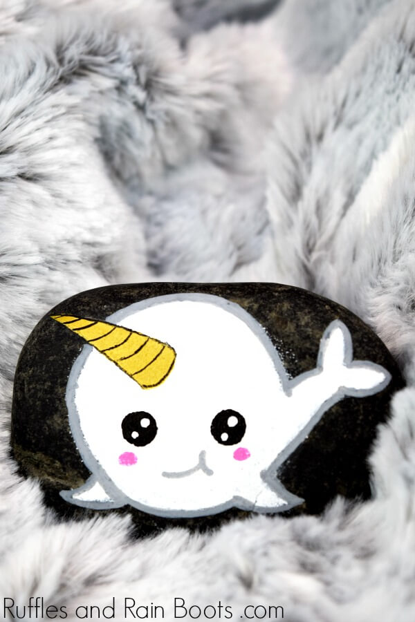 white narwhal rock painting on dark stone with a fuzzy gray background