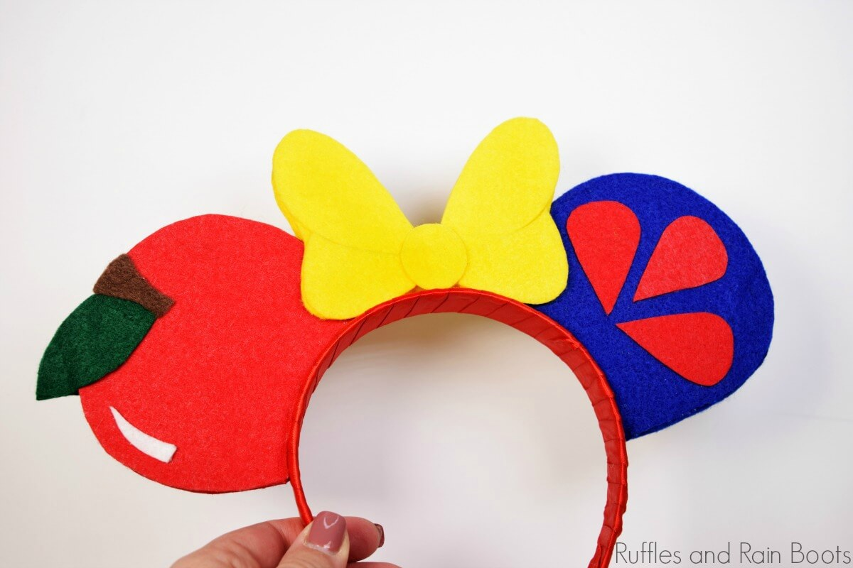 hand holding Snow White Mickey Mouse ears headband