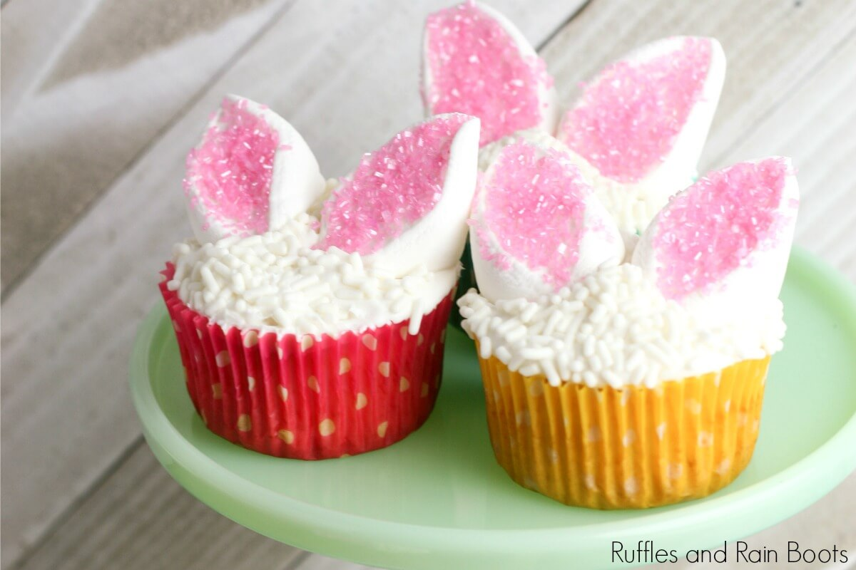 three Easter bunny cupcakes on a green plate with a white background