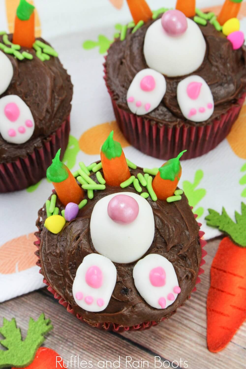 close up of bunny Easter cupcakes on carrot cloth and wooden table